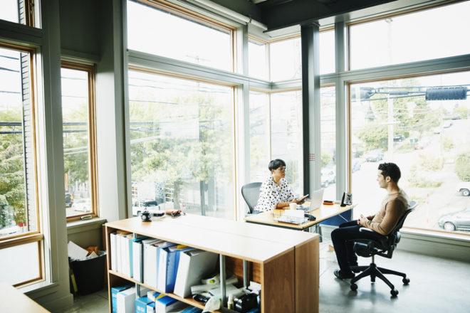 小さなオフィスで男性と女性が打ち合わせをしている