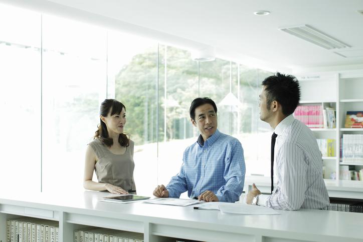 オフィスで社員同士が会話している