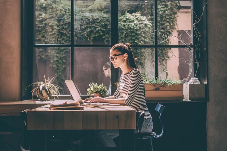 窓際でパソコン仕事をしている女性